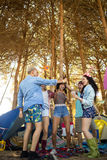 Cheerful male friends toasting beer bottles at campsite. Cheerful male friends toasting beer bottles while standing on field at campsite Royalty Free Stock Photos