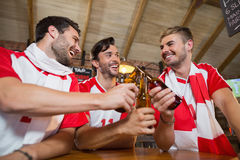 Cheerful male friends toasting beer bottles. In pub Royalty Free Stock Photos