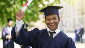 Cheerful male graduate showing certificate for camera and smiling, success royalty free stock photo