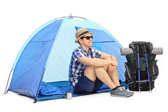 Cheerful male hiker sitting in front of a tent Royalty Free Stock Photos