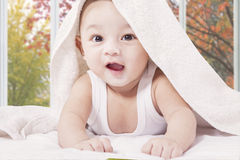 Cheerful male infant under a towel. Closeup of excited male infant crawling on the bed under a towel while smiling at the camera Royalty Free Stock Photos
