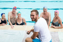 Cheerful male instructor assisting senior swimmers. At poolside Royalty Free Stock Photos