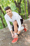 Cheerful male jogger tying shoes. Happy young man ties shoelaces before running. He is kneeling and wearing earphones. Runner is looking at camera and smiling Royalty Free Stock Photos
