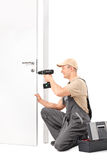 Cheerful male locksmith installing a door lock Royalty Free Stock Images
