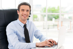 Cheerful male operator. Side view of cheerful young man in headset looking at camera and smiling while using laptop Royalty Free Stock Images