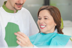 Cheerful male orthodontist is working with patient Royalty Free Stock Images