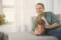 Cheerful male owner relaxing on sofa with pet stock photos
