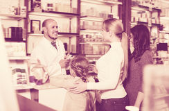 Cheerful male pharmacist helping customers. Cheerful male pharmacist wearing white coat standing next to shelves with medicine and helping customers Royalty Free Stock Image
