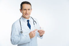 Cheerful male practitioner holding box with pills Stock Photo