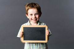 Cheerful male preschooler proud to learn with writing slate. Portrait of a happy 5-year old male preschooler proud to learn at school, enjoying holding a copy stock images