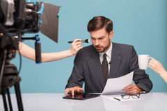 Cheerful male reporter before telling some news. Attractive young tv newscaster is preparing for report. He is sitting at the desk and using a tablet with stock photo