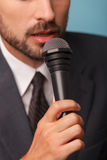 Cheerful male reporter is telling some news. Close up of male tv journalist speaking into the microphone. The man is standing and wearing a suit royalty free stock images