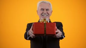 Cheerful male retiree in suit presenting red giftbox on camera, birthday present. Stock footage stock footage
