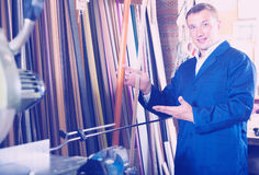Cheerful male seller in picture framing studio with wooden detai. Cheerful male seller standing in picture framing studio with wooden details Royalty Free Stock Photos