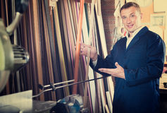 Cheerful male seller in picture framing studio with wooden detai. Cheerful male seller standing in picture framing studio with wooden details Stock Image
