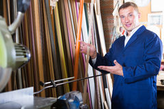 Cheerful male seller in picture framing studio with wooden detai Royalty Free Stock Photos