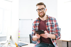 Cheerful male sitting and holding tablet in the office Royalty Free Stock Photo