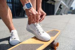 Cheerful male skateboarder lacing his shoes. Close up of male legs standing on skateboard. Man is tying laces on his sneakers. He has smart watch on his hand Stock Photography