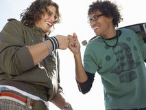 Cheerful Male Skateboarders Giving A Fist Bump Stock Image