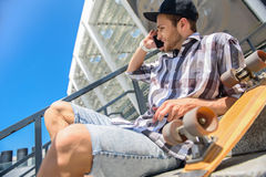 Cheerful male skater entertaining with telephone. Carefree young man is sitting and resting on staircase near skateboard. He is talking on phone and smiling Stock Photography