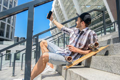 Cheerful male skater photographing himself on phone. Carefree young man is making selfie on smartphone. He is looking at camera and smiling. Guy is sitting on Stock Image