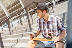 Cheerful male skater relaxing on staircase. Joyful young man is sitting on steps and smiling. He is holding skateboard and looking aside with happiness Royalty Free Stock Image