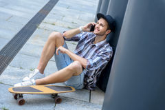 Cheerful male skater using smartphone. Joyful young man is talking on mobile phone and smiling. He is sitting on flooring near skateboard outdoors Stock Image