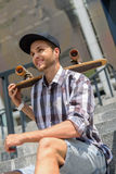 Cheerful male skater waiting for someone. Joyful young man is sitting on staircase with his skateboard. He is looking forward with anticipation and laughing Royalty Free Stock Image