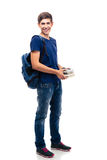 Cheerful male student holding books. Full length portrait of a cheerful male student with backpack holding books isolated on a white background. Looking at Stock Images