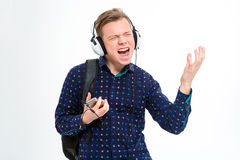 Cheerful male student listening music in headphones. Portrait of a cheerful male student listening music in headphones  on a white background Stock Photo