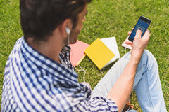 Cheerful male student messaging on phone. Getting message. Young man is using smartphone. He is sitting on grass near textbooks and relaxing. Guy is wearing Royalty Free Stock Image