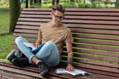 Cheerful male student reading literature on bench in park. Portrait of happy young man studying in campus outdoors. He is looking at book with interest and Royalty Free Stock Photography