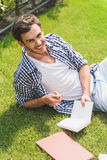 Cheerful male student relaxing on lawn. Happy young man is studying in nature. He is lying on grass and smiling Stock Image