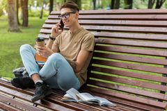 Cheerful male student using smartphone for communication. Portrait of positive young man talking on mobile phone and laughing. He is sitting on bench outdoors Stock Image