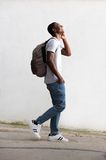 Cheerful male student walking and talking on cell phone Royalty Free Stock Image