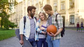 Cheerful male students flirting and hugging pretty female, pick-up tricks. Stock photo royalty free stock photos