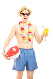 Cheerful male in swimming shorts, holding a beach ball and cockt Royalty Free Stock Images