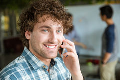 Cheerful male talking on cellphone while his team working. Cheerful attractive curly young male in blue plaid shirt talking on cellphone while his team working Stock Photo