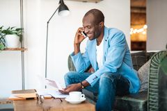 Cheerful male talking by phone. Portrait of beaming businessman telling by mobile while working with graphics. He sitting on sofa Stock Image