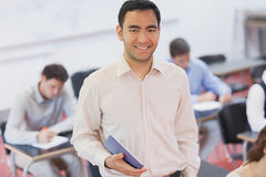Cheerful male teacher posing in his classroom holding a tablet Stock Photography