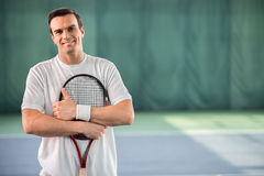 Cheerful male tennis player enjoying game. My favorite hobby is tennis. Portrait of happy young man standing on tennis court and hugging racket with joy. He is Stock Photo