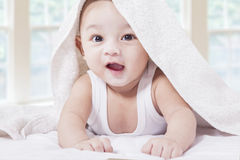 Cheerful male toddler playing on bed. Portrait of happy male baby playing on bed and smiling at the camera under a towel Royalty Free Stock Photography