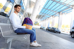 Cheerful male tourist expecting public transport Royalty Free Stock Photo