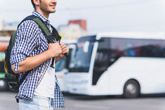 Cheerful male tourist ready to travel. Joyful young man is preparing for departure. He is standing on bus station and laughing. Traveler is carrying backpack Royalty Free Stock Image