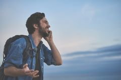 Cheerful male tourist speaking by cellphone at seaside. You will not believe where I am now. Happy young man is talking on mobile phone while hiking with Royalty Free Stock Photo