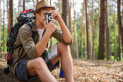 Cheerful male traveler taking photo of forest Stock Photo