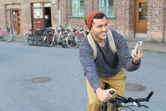 Cheerful male trying to find directions on his smart phone.  Royalty Free Stock Image