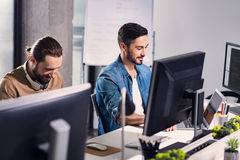 Cheerful male typing on notebook computer keyboard. Side view smiling bearded men working on laptop while telling with comrade in office Royalty Free Stock Image