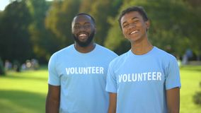 Cheerful male volunteers smiling on camera, eco project participation, charity stock footage