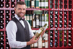 Cheerful male waiter is working in wine-cellar. Attractive young sommelier is holding a bottle of white wine. He is standing in liquor store and smiling. The man Stock Photo